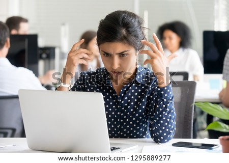 Upset indian female worker sitting at desk in office looking at pc screen feels unhappy and shocked. Millennial hindu woman reading unpleasant notification having system fault and big troubles concept