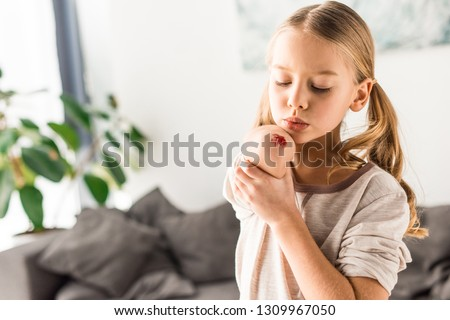 Upset kid blowing on wound at home Foto d'archivio ©