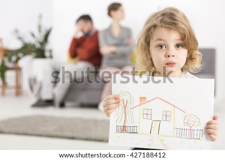 Upset little boy holding a drawing of a house, with his parents sitting angry on a couch in the blurry background #427188412