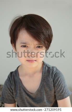 Upset little boy, holding in his emotions. Tearful child. Dramatic kid. Angry young youth with tears in his eyes. Childhood depression concept. Children\'s mental health. Working through problems.