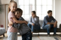 Upset little girl and boy, sister and brother hugging, suffering from parents quarrel close up, family conflict, offended mother and father ignoring each other after argument, children and divorce