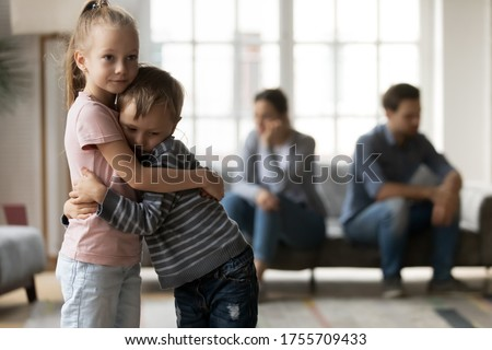 Upset little girl and boy, sister and brother hugging, suffering from parents quarrel close up, family conflict, offended mother and father ignoring each other after argument, children and divorce Foto stock ©