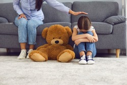 Upset little girl crying on floor near teddy bear while mother comforting her at home. Parent soothing her unhappy child