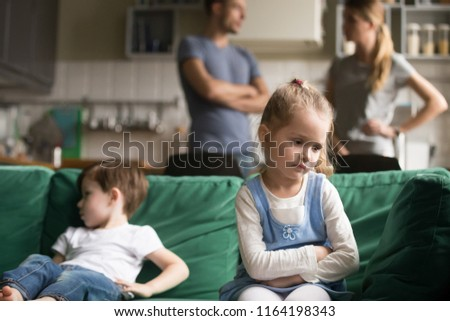 Upset little girl feeling sad after fight with brother sitting on sofa with worried parents on background, sulky frustrated sister ignoring child boy disinterested or bored, siblings rivalry concept #1164198343