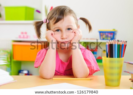 Upset little girl sitting with colorful pencils at desk