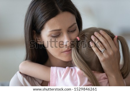 Upset loving mother embracing, comforting little daughter close up, expressing love and support, family enjoying tender moment, trusted good relationship, child custody, new mom for adopted child