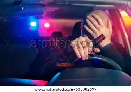 Upset male driver is caught driving under alcohol influence. Man covering his face from police car light.