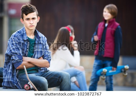 Upset male teen sitting aside of girlfriend talking with boy outdoors