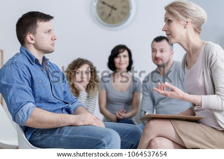 Upset man sitting in group therapy and listening to the psychologist with concerned family in the background
