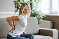 Upset mature woman suffering from backache, unhappy senior blonde sitting on a sofa at living room, feeling discomfort because of pain in back.
