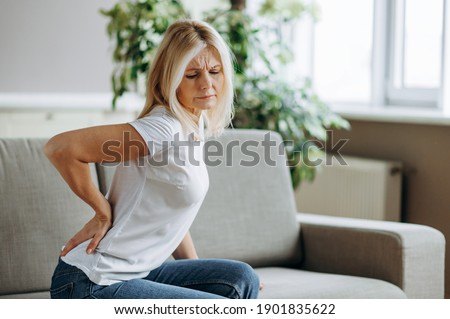 Upset mature woman suffering from backache, unhappy senior blonde sitting on a sofa at living room, feeling discomfort because of pain in back. Foto stock ©