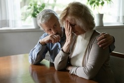 Upset middle aged family couple grieving, getting bad news about health problem. Senior husband giving support to crying mature wife, hugging and consoling unhappy woman with empathy and compassion