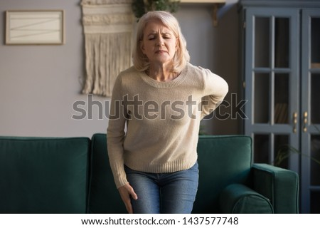 Upset middle aged old woman touching sore spine feel hurt sudden back pain ache injury standing at home, mature senior grandmother having lower lumbago backache osteoarthritis, backache concept
