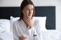 Upset millennial female look in distance crying feeling down distressed get negative pregnancy results on plastic medical test, sad young woman depressed with infertility, health problems concept