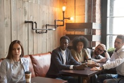 Upset millennial girl ignoring multiracial people trying to cheer her up, sitting at next table in coffeeshop, frustrated offended woman not talking with friends making peace with her in cafe