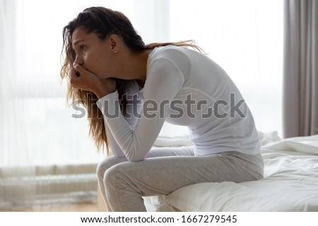 Upset millennial girl sit on bed in bedroom lost in thoughts thinking pondering of problem solution, depressed unhappy young woman look in distance suffer from depression, having personal problems