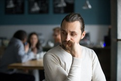 Upset millennial outsider feel offended lack company, young outcast guy suffer from discrimination, jealous of friends hang out together in café, envious male loner depressed sit alone in coffeeshop