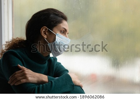 Upset millennial woman in medical facemask sit look in window feeling lonely quarantine alone at home. Unhappy sad young Caucasian female in facial mask suffer from covid-19 pandemics. Corona concept.