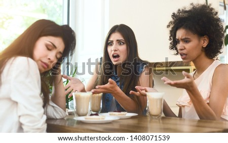 Upset multiethnic girls having an argument with third friend in cafe, panorama, free space
