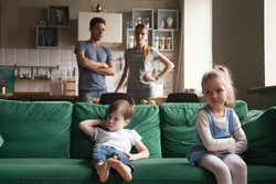 Upset offended sister, daughter sitting separately on couch with arms crossed with toddler brother on couch, sofa after fight about tv channel, cartoon choice, little girl and boy ignoring each other