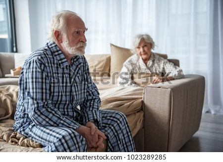 Upset old man sitting on bed with sad look. His woman sitting in bed under the blanket and looking at him with sympathy