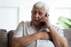 Upset older man touching chest, calling emergency, talking on phone, unhappy mature male having heart attack, lonely grandfather suffering from heartache disease at home, feeling pain, sitting alone