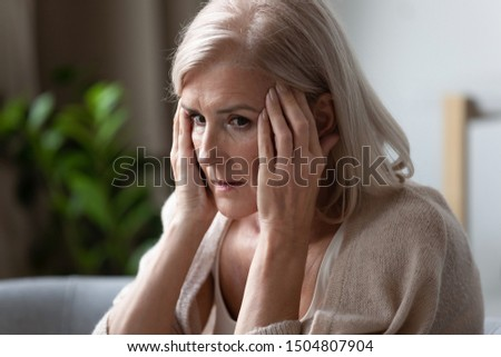 Upset older woman touching temples, feeling bad, pressure, sitting alone, mental disorder or dementia, frustrated mature female looking in distance, thinking about emotional or health problem