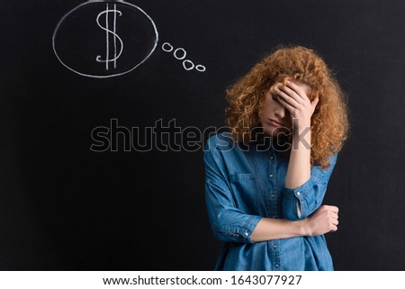upset pensive girl with dollar sign in thought bubble on chalkboard