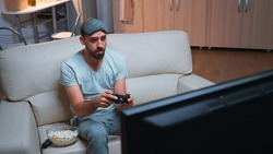 Upset pro gamer losing videogamer competition using wireless joystick during gaming competition. Disappointed player sitting in front of television on sofa making loser gesture late at night