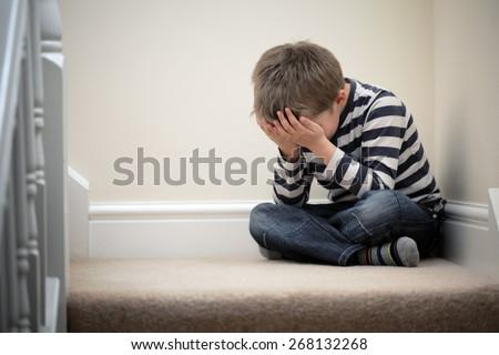 Upset problem child with head in hands sitting on staircase concept for bullying, depression stress or frustration #268132268