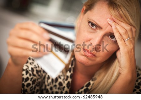 Upset Robed Woman Glaring At Her Many Credit Cards.