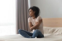 Upset sad African American woman sitting in bed alone, hugging herself, feeling lonely, unhappy girl has psychological troubles, trauma, thinking about problem in bedroom, unwanted pregnancy