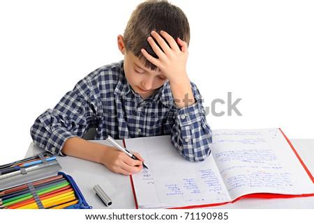 Upset schoolboy doing homework isolated on white