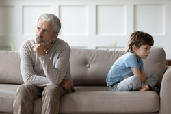 Upset senior grandfather and small 6s grandson sit back to back on couch avoid talking after fight. Unhappy elderly grandparent and little boy child have misunderstanding. Generation gap concept.