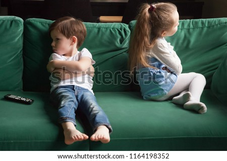 Upset siblings boy and girl sulking sitting with arms crossed on sofa not talking, kids brother sister ignoring each other after fight about tv channel choice, children conflicts and rivalry concept