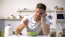 Upset single man eating tasteless cereals for breakfast, lack of appetite