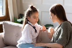 Upset small schoolgirl having trustful conversation with compassionate young mother, sitting together on sofa. Wise mommy comforting soothing little child daughter, overcoming problems at home.