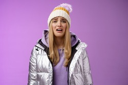 Upset sobbing miserable cute blond woman in silver stylish jacket hat crying whining unhappy feel sadness distress look disappointed complaining cruel life, unlucky standing purple background