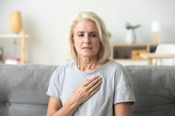 Upset stressed mature middle aged woman feeling pain ache touching chest having heart attack, sad worried senior older lady suffers from heartache at home, infarction or female heart disease concept