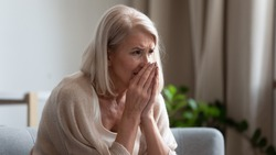 Upset stressed mature woman crying, sitting alone on couch at home, suffering from anxiety or disease, feeling lonely and unwell, desperate frustrated older female widow mourning, grieving, bad news