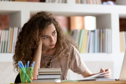 Upset thoughtful female millennial student sit at desk unable to study distracted thinking of something, pensive abstracted girl look through handbooks prepare in library consider problem or issue