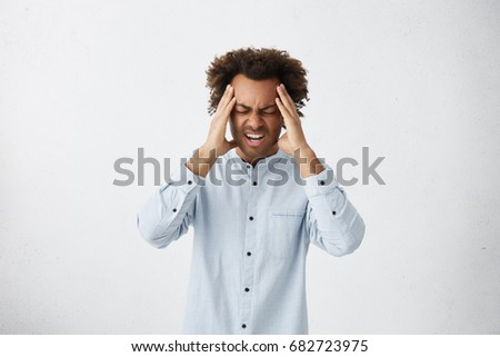 Upset unhappy dark-skinned male student squeezing head with hands, writhing in pain, suffering from headache after he spent sleepless night preparing for exams. People, stress, tension and migraine #682723975