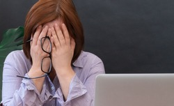 Upset Woman closed your face of hands near her workplace with laptop