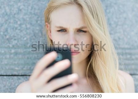 Upset woman holding a cellphone.