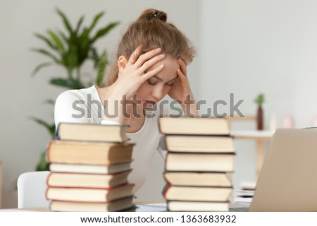 Upset woman sitting with closed eyes among textbooks and laptop, holding head in hands, annoyed by learning, feeling fatigue and despair, preparing for exam, writing diploma or coursework