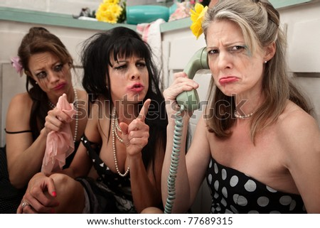 Upset woman with drunk friends on phone in kitchen