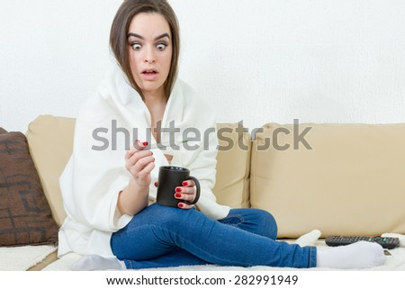 Upset woman with thermometer sick colds, flu, fever and migraine in bed with cup of tea or coffee. Girl with high temperature and headache virus. Female caught cold covered with white blanket at home.