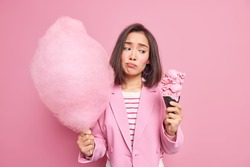 Upset young Asian woman holds delicious ice cream and cotton candy feels temptation to eat sweet food cannot refuse eating tasty dessert dressed in formal jacket isolated over pink background