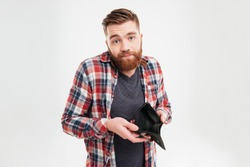 Upset young bearded man in plaid shirt holding empty wallet over white background