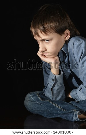 upset young boy on a black background